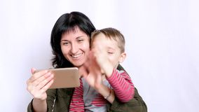 A happy young mother and child are looking at the screen of a smartphone and waving their hands while communicating on stock video footage