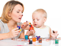 Happy young mother with a child paint by hands. Royalty Free Stock Image