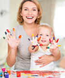 Happy young mother and child with painted hands. Royalty Free Stock Image