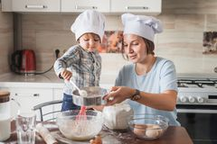 Happy young mother and child preparing dough for baking. At kitchen royalty free stock photo