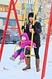 Happy young mother and child on a swing, cold winter Stock Photography