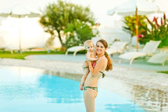 Happy young mother with cute baby standing in pool Royalty Free Stock Photo