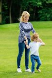 Happy young mother with cute little son holding hands while walking on green lawn. In park royalty free stock image