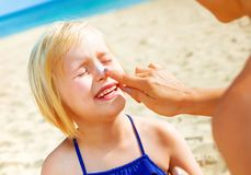 Happy young mother and daughter on beach applying SPF stock photo