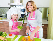 Happy young mother with daughter cooking. Stock Photography