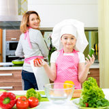 Happy young mother with daughter cooking. Royalty Free Stock Photos