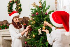 Mother and daughter decorating christmas tree. Happy young mother and daughter decorating christmas tree together Royalty Free Stock Photos