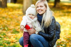 Happy young mother with daughter in park among yellow trees Stock Photos