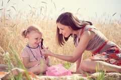 Happy young mother with daughter playing field Royalty Free Stock Photo