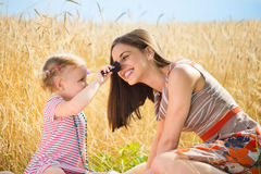 Happy young mother with daughter playing field Royalty Free Stock Image