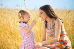 Happy young mother with daughter playing field Stock Photo