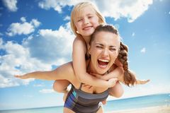 Happy young mother and daughter on seacoast rejoicing. Happy young mother and daughter in swimsuit on the seacoast rejoicing stock image