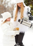 Happy young mother with daughter on winter picnic Stock Image