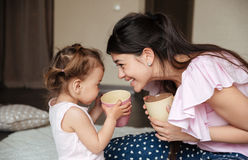 Happy young mother drinking tea with her little daughter Stock Photo