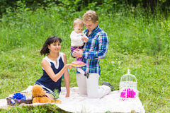 Happy young mother and father with their baby daughter relaxing on a blanket in a park celebrating with birthday cake Stock Photo