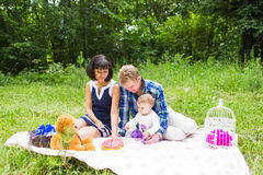 Happy young mother and father with their baby daughter relaxing on a blanket in a park celebrating with birthday cake Stock Photography