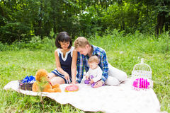 Happy young mother and father with their baby daughter relaxing on a blanket in a park celebrating with birthday cake Stock Image