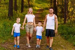 Happy young mother and father and two children summer outdoors. Happy family in white t-shirts walking through the woods. Holding hands stock photo