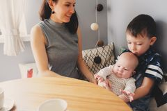 Happy young mother having breakfast in modern kitchen with her baby daughter and kid son Royalty Free Stock Photo