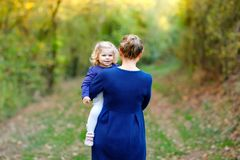 Happy young mother having fun cute toddler daughter, family portrait together. Woman with beautiful baby girl in nature royalty free stock images