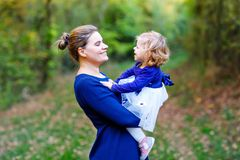 Happy young mother having fun cute toddler daughter, family portrait together. Woman with beautiful baby girl in nature stock image