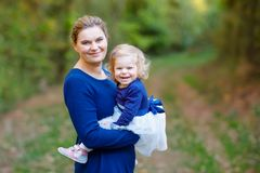Happy young mother having fun cute toddler daughter, family portrait together. Woman with beautiful baby girl in nature royalty free stock image