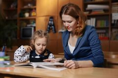 Happy Young Mother Helping Her Daughter While Studying At Home. Happy Young Mother Helping Her Daughter While Studying At Royalty Free Stock Photo