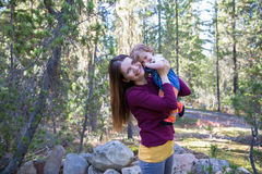 Happy young mother with her baby daughter in the mountain forest. Happy young mother holding her baby daughter on hands. Mountain forest background Royalty Free Stock Photography