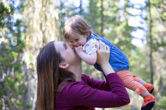 Happy young mother with her baby daughter in the mountain forest. Happy young mother holding her baby daughter on hands, flying high, throwing up. Mountain Stock Image