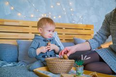Happy young mother and her baby son playing with walnuts royalty free stock image