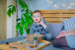 Happy young mother and her baby son playing with walnuts royalty free stock photography