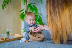 Happy young mother and her baby son playing with walnuts stock images