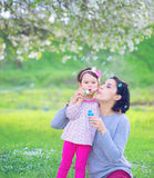 Happy young mother and her daughter blowing soap bubbles Royalty Free Stock Image