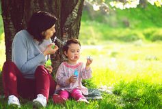 Happy young mother and her daughter blowing soap bubbles Royalty Free Stock Images