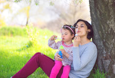 Happy young mother and her daughter blowing soap bubbles Stock Photo
