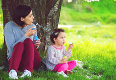 Happy young mother and her daughter blowing soap bubbles in the park Royalty Free Stock Images
