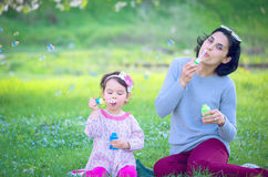 Happy young mother and her daughter blowing soap bubbles Stock Images