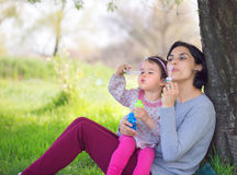 Happy young mother and her daughter blowing soap bubbles. In park Royalty Free Stock Photography