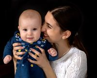 Happy young mother with her daughter on her hands on a black bac. Beautiful young mother with a little daughter in her arms, studio on a black background. The royalty free stock photo
