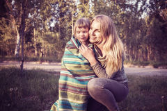 Happy young mother and her little daughter dressed in a blanket Royalty Free Stock Images