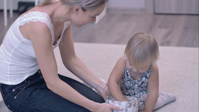 Happy young mother and her little daughter exploring the jewelry box sitting on the carpet stock video