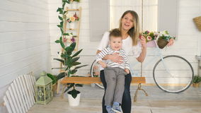 Happy young mother with her little son sits on rope swing and play together in their bedroom stock video