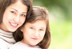 Happy young mother with her small daughter. Beautiful and happy young mother with her small daughter outdoors. Both women and small girl happy and smiling Royalty Free Stock Image