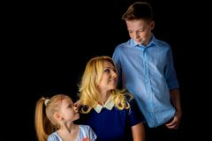 Happy young mother with her son and daughter on a black backgrou. Beautiful young mother with her son and daughter in the studio on a black background. The royalty free stock image