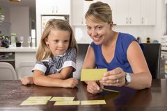 Happy young mother and her sweet and beautiful little daughter playing card game at home kitchen smiling and having fun together. In education and family Royalty Free Stock Image