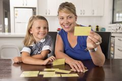 Happy young mother and her sweet and beautiful little daughter playing card game at home kitchen smiling and having fun together. In education and family Stock Image