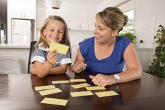 Happy young mother and her sweet and beautiful little daughter playing card game at home kitchen smiling and having fun together. In education and family Stock Photos