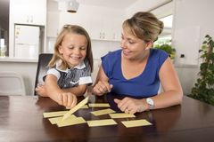 Happy young mother and her sweet and beautiful little daughter playing card game at home kitchen smiling and having fun together. In education and family Royalty Free Stock Images