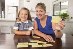 Happy young mother and her sweet and beautiful little daughter playing card game at home kitchen smiling and having fun together stock photography