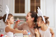 Happy young mother and her two little daughters with white rabbit`s ears on their heads have fun while dyeing the eggs royalty free stock photography